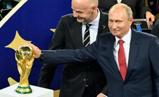 Russia's President Vladimir Putin caresses the World Cup trophy