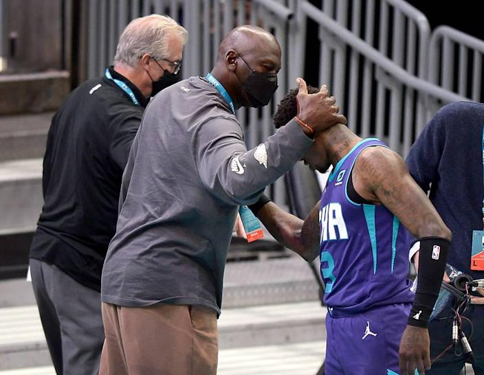 Charlotte Hornets team owner Michael Jordan, center, reaches out to embrace guard Terry Rozier, right, following the Hornets' March 11th win over Detroit.