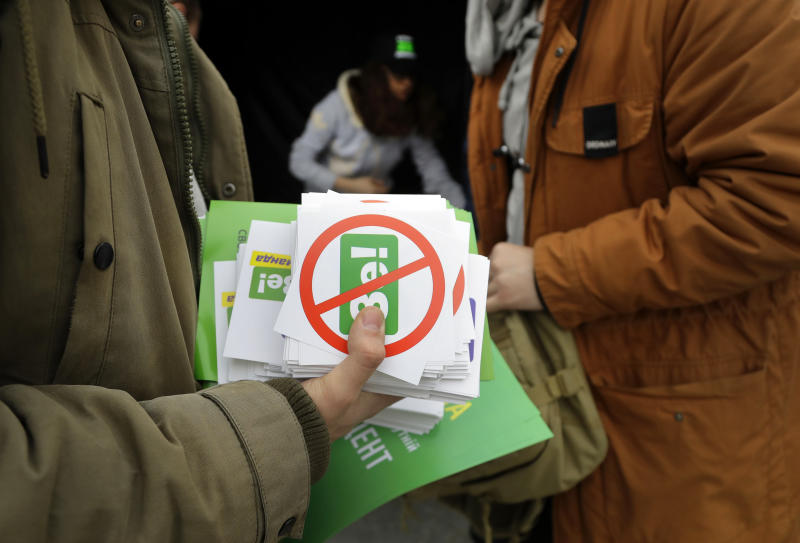 Opponents of Ukrainian comedian and presidential candidate Volodymyr Zelenskiy prepare to distribute stickers in downtown Kiev, Ukraine, Wednesday, April 17, 2019. The second round of presidential vote in Ukraine will take place on April 21. (AP Photo/Sergei Grits)