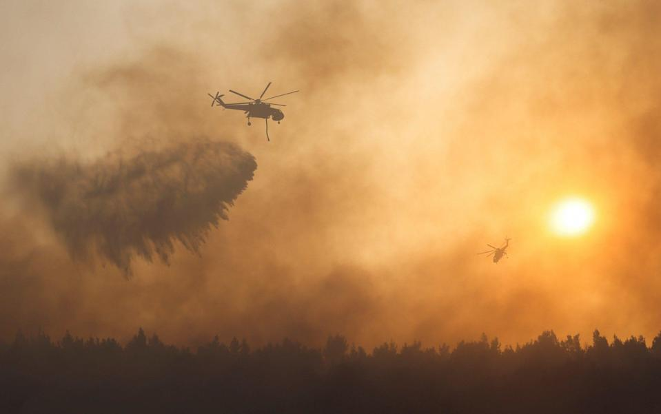 A firefighting helicopter makes a water drop as a wildfire continues to rage at Varympompi suburb north of Athens - REUTERS