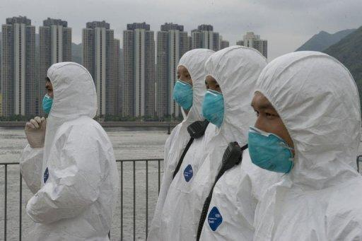 Rescuers wearing environmental suits look on while participating in a nuclear accident test in Hong Kong