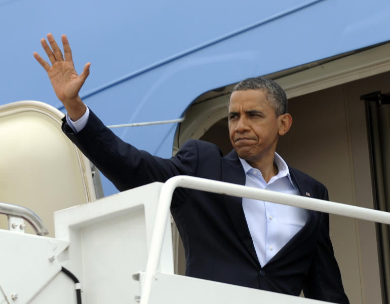 President Barack Obama waves from the steps of Air Force One at Andrews Air Force Base, Md., Sunday, July 22, 2012. Obama is traveling to Aurora, Colo., to visit with families of victims of the movie theater shooting as well as local officials. (AP Photo/Susan Walsh)