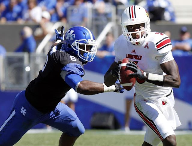 Louisville's Teddy Bridgewater, right, eludes the grasp of Kentucky's Jason Hatcher in the fourth quarter of an NCAA college football game on Saturday, Sept. 14, 2013, in Lexington, Ky. Louisville won 27-13. (AP Photo/James Crisp)
