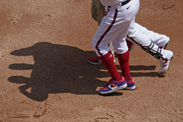 Chicago White Sox's Luis Robert, center, leaves with a team trainer and first base coach Daryl Boston during the first inning of a baseball game against the Cleveland Indians in Chicago, Sunday, May 2, 2021. (AP Photo/Nam Y. Huh)