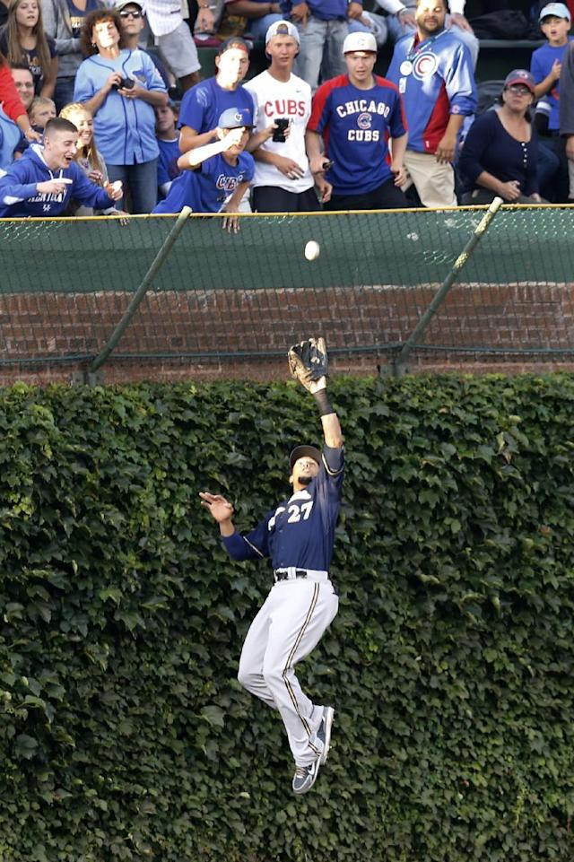 Milwaukee Brewers center fielder Carlos Gomez makes a leaping catch on a fly ball hit by Chicago Cubs' Javier Baez at the ivy in left center field, during the first inning of a baseball game Tuesday, Aug. 12, 2014, in Chicago. (AP Photo/Charles Rex Arbogast)