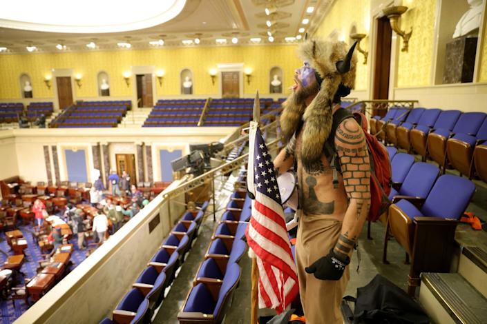 A shirtless man covered in tattoos, wearing a fur Viking hat and carrying an American flag yells inside the Senate chamber.