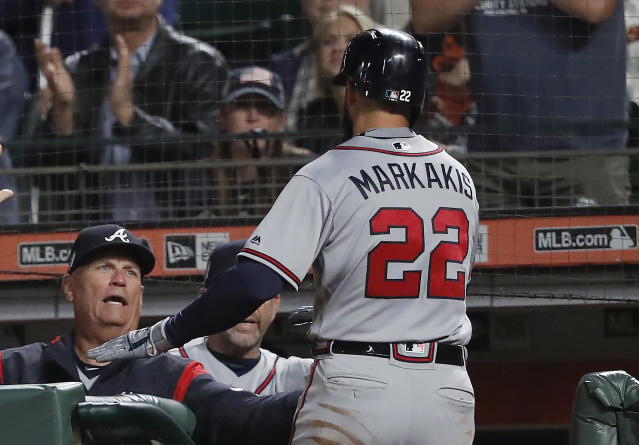 Atlanta Braves' Nick Markakis (22) is congratulated by manager Brian Snitker, left, after scoring a run against the San Francisco Giants on a sacrifice fly by Ender Inciarte during the fourth inning of a baseball game in San Francisco, Tuesday, Sept. 11, 2018. (AP Photo/Tony Avelar)