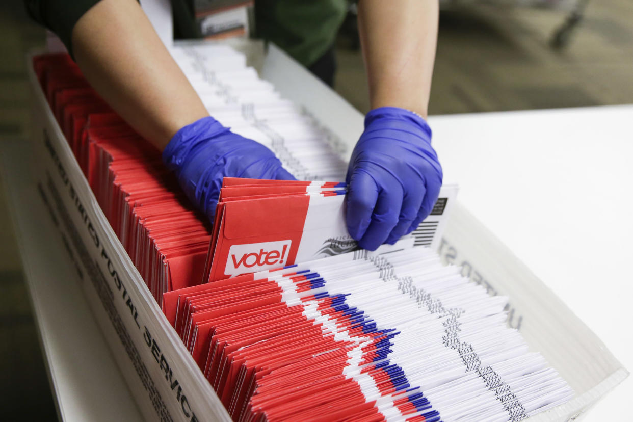 Election workers sort vote-by-mail ballots for the presidential primary at King County Elections in Renton, Wash., in March 2020.