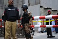EDITORS NOTE: Graphic content / Police and paramilitary soldiers stand guard near a body of an alleged gunman at the main entrance of the Pakistan Stock Exchange building in Karachi on June 29, 2020. - Gunmen attacked the Pakistan Stock Exchange in Karachi on June 29, with four of the assailants killed, police said. (Photo by Asif HASSAN / AFP) (Photo by ASIF HASSAN/AFP via Getty Images)