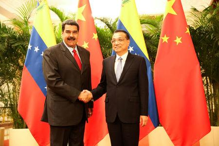 Venezuela's President Nicolas Maduro and Chinese Premier Li Keqiang shake hands during their meeting in Beijing