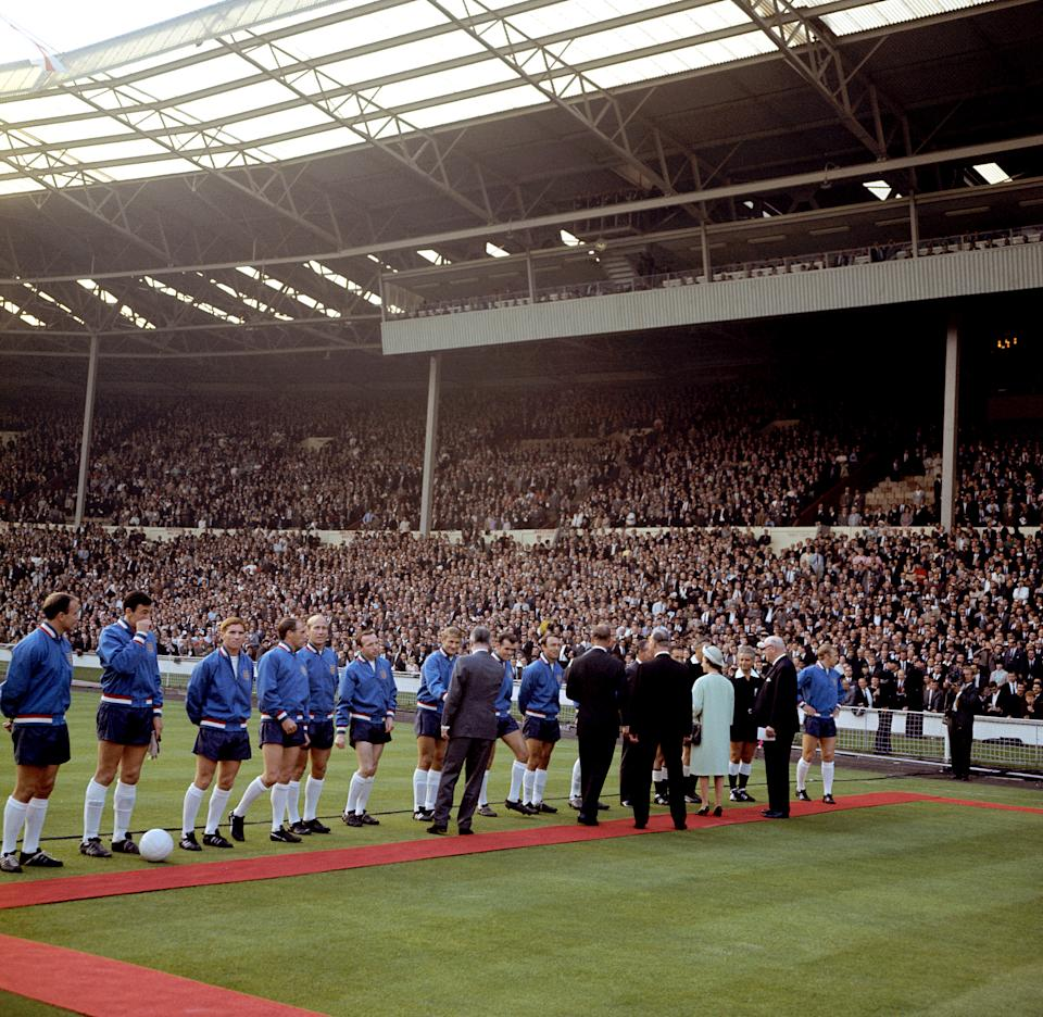 HRH Queen Elizabeth II (fourth r) is introduced to the England team by FIFA President Sir Stanley Rous (second r) before the opening match of the Finals. The England players are (l-r) George Cohen, Gordon Banks, Alan Ball, Ray Wilson, Bobby Charlton, Nobby Stiles, Roger Hunt, John Connelly, Jimmy Greaves, Jack Charlton (hidden), Bobby Moore (far r) (Photo by PA Images via Getty Images)