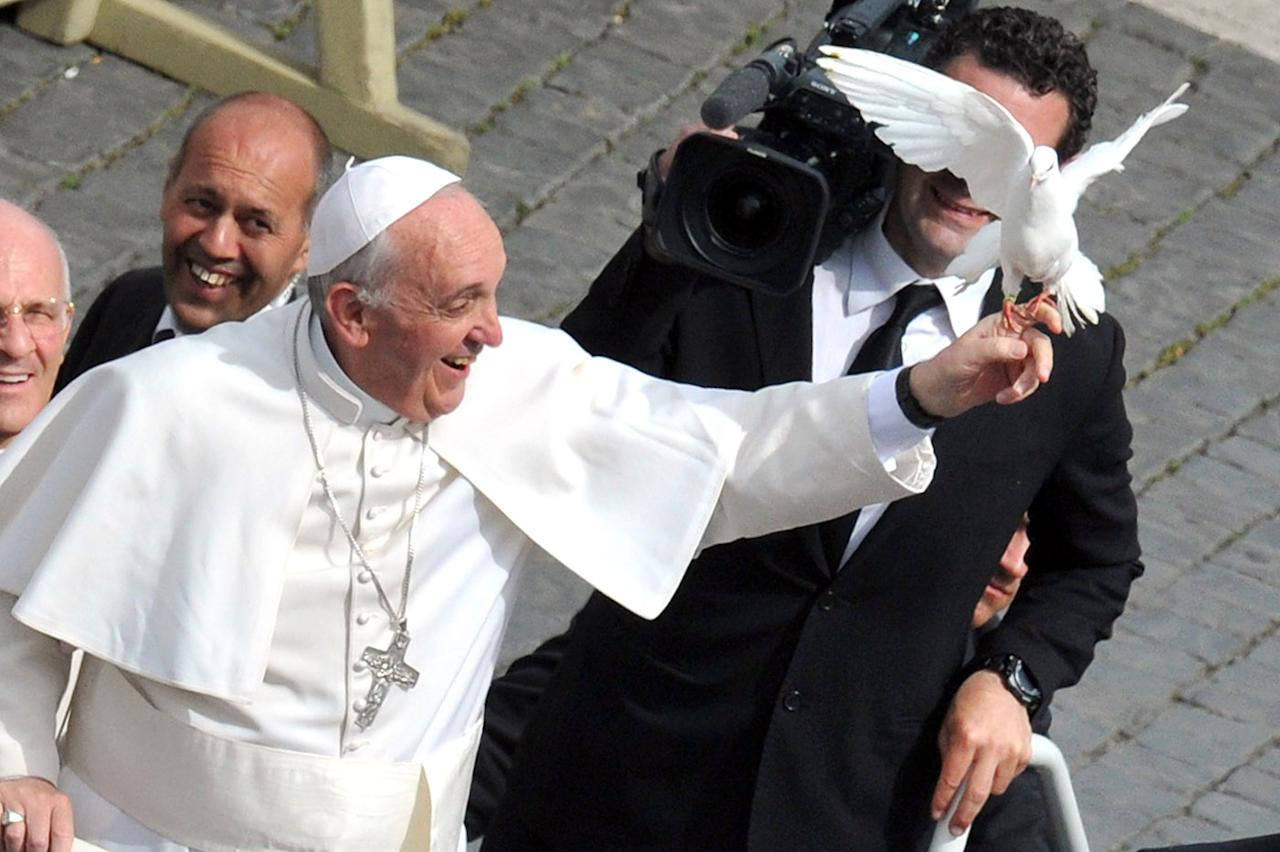 Pope Francis grabs a dove as he arrives for his weekly general audience in St Peter's Square on May 15, 2013 at the Vatican. AFP PHOTO / TIZIANA FABI