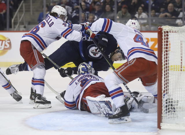 Winnipeg Jets center Adam Lowry (17) is hit by New York Rangers right wing Mats Zuccarello (36) after trying to score on goaltender Henrik Lundqvist (30), as defenseman Neal Pionk (44) defends the crease during the second period of an NHL hockey game Tuesday, Feb. 12, 2019, in Winnipeg, Manitoba. (Trevor Hagan/The Canadian Press via AP)