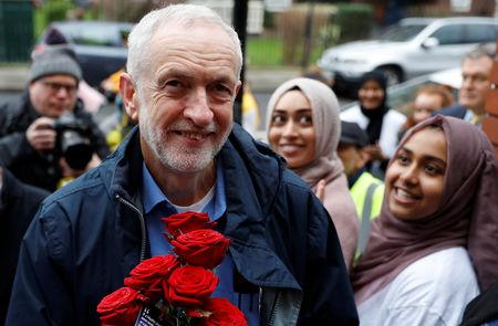Party leader Jeremy Corbyn is greeted by young women and red roses during a visit to Finsbury Park Mosque on Visit My Mosque day in London