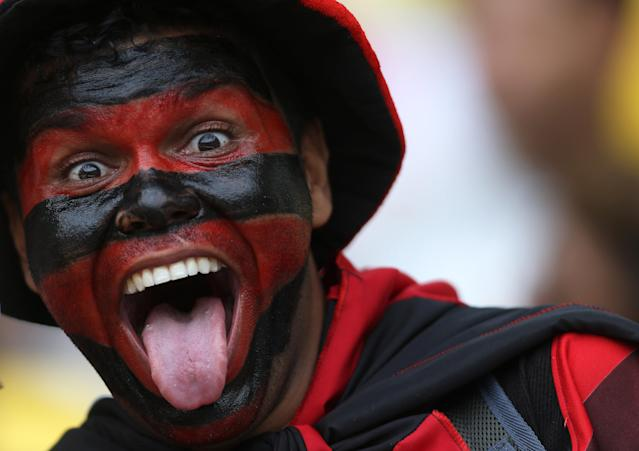 In this April 13, 2014 photo, a fan with his face painted in the colors of Flamengo's soccer team poses before a Rio de Janeiro state championship final soccer game with Vasco at Maracana stadium in Rio de Janeiro, Brazil. Brazil expects a total of 3.7 million tourists during the World Cup, with 600,000 of those arriving from abroad. (AP Photo/Leo Correa)