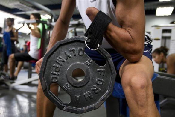Willy Martinez, 27, a member of the Venezuelan Paralympics team, lifts weights during training in Caracas April 24, 2012. Martinez was a high-ranked Venezuelan boxer at the age of 18 when an enraged relative cut off his hand with a machete. Now he is training to qualify as a sprinter for the London Paralympics.
