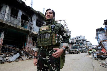 Captain Arnel Carandang of the Philippine army 1st scout ranger battalion past damaged houses and building in Sultan Omar Dianalan boulevard at Mapandi district in Marawi city