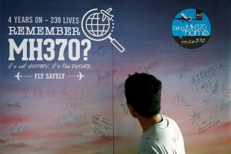 FILE PHOTO: Man looks at message board for passengers onboard missing MH370 in Kuala Lumpur