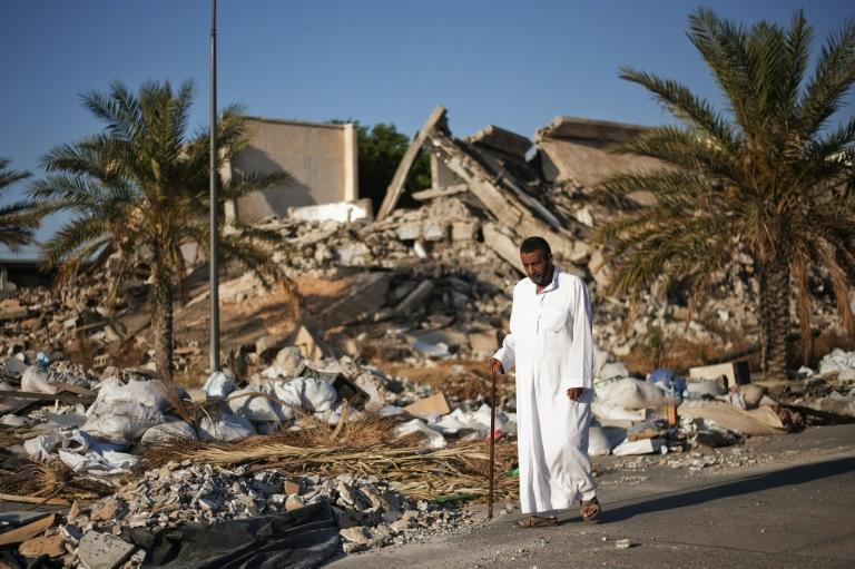 A man walks past a destroyed building at Libyan dictator Moamer Kadhafi's former headquarters in Tripoli in a picture taken in 2012, one year after the ruler was ousted and killed in a NATO-backed uprising