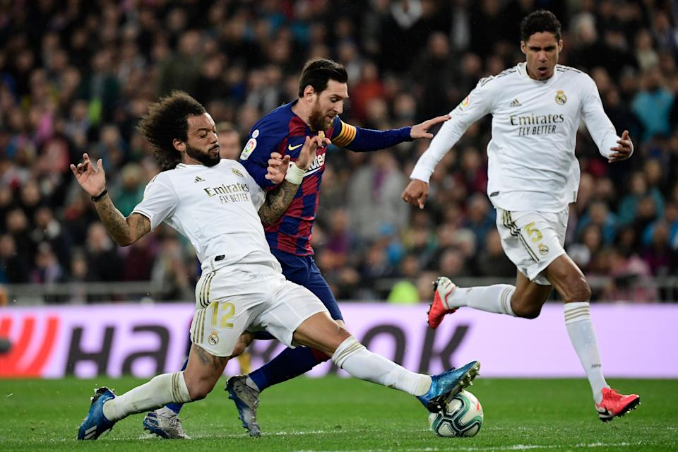 Real Madrid's Brazilian defender Marcelo (L) vies with Barcelona's Argentine forward Lionel Messi during the Spanish League football match between Real Madrid and Barcelona at the Santiago Bernabeu stadium in Madrid on March 1, 2020. (Photo by JAVIER SORIANO / AFP) (Photo by JAVIER SORIANO/AFP via Getty Images)