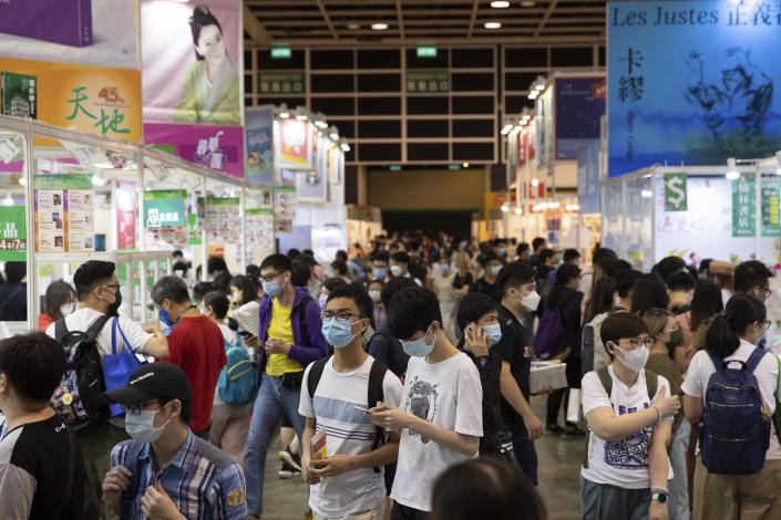 People visit the annual book fair in Hong Kong Wednesday, July 14, 2021. Booksellers at Hong Kong's annual book fair are offering a reduced selection of books deemed politically sensitive, as they try to avoid violating a sweeping national security law imposed on the city last year. (AP Photo/Matthew Cheng)