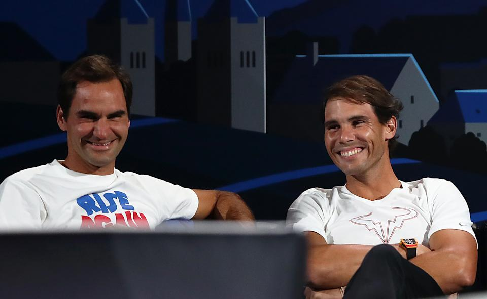 Rafael Nadal and teammate Roger Federer share a joke during a singles match at the Laver Cup.