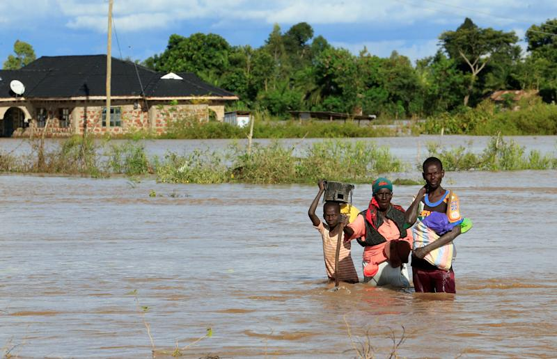 Residents wade through the waters after their home was flooded after the River Nzoia burst its banks and due to heavy rainfall and the backflow from Lake Victoria, in Budalangi within Busia County, Kenya May 3, 2020. REUTERS/Thomas Mukoya