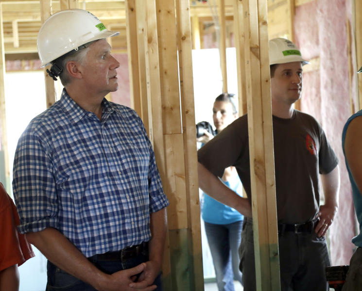 FILE - In this Sept. 26, 2018 file photo republican Mark Harris, left, and democrat Dan McCready, right, listen to instructions during a Habitat For Humanity building event in Charlotte, N.C. North Carolina's Republican Party chairman said Tuesday, Dec. 11, 2018 that the state should order a new election in an unresolved congressional race if an affidavit alleging some early voting totals were improperly shared before Election Day is accurate. (AP Photo/Chuck Burton, file)