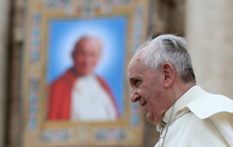 FILE PHOTO: Pope Francis passes next to a tapestry of the late Pope John Paul II, as he leaves at the end of his weekly general audience at St. Peter's Square