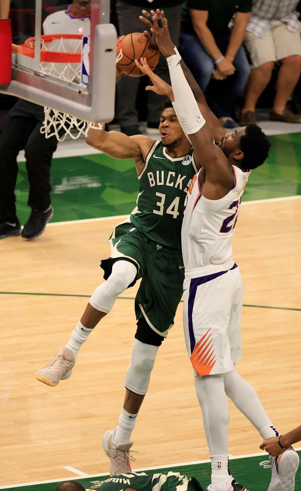 Deandre Ayton (right) fouls Giannis Antetokounmpo in the second half of Game 3. Ayton was limited to just 24 minutes because of foul trouble.