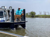 A volunteer and a dog trained to search for cadavers join others looking for survivors of the Seacor Power, a lift boat that capsized on April 13 off the Louisiana coast. Volunteers have been searching by air and boat for any sign of those still missing. (AP Photo/Rebecca Santana)