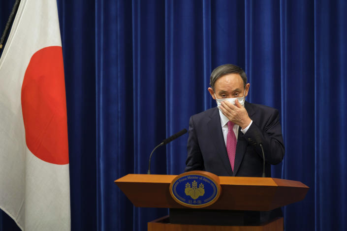 Japan's Prime Minister Yoshihide Suga adjusts a face mask after a press conference on the COVID-19 situation in Japan at the prime minister's office in Tokyo, Friday, Dec. 25, 2020. Suga said on Friday he will seek a legislation to allow the government to impose legally-binding business restriction orders in return for compensation and punish violators as Japan struggles to slow the ongoing upsurge of the coronavirus cases ahead of the holiday season while people are becoming less cooperative. (Nicolas Datiche/Pool Photo via AP)