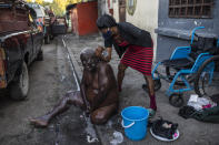 Marie Joseph bathes her friend Jean Robert outside a shelter for the internally displaced where they live due to police violence in Port-au-Prince, Haiti, Thursday, Sept. 16, 2021. Most of the population of Port-au-Prince has no access to basic public services, no drinking water, electricity or garbage collection. (AP Photo/Rodrigo Abd)