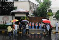 Municipal workers wearing personal protective equipment suits (PPE) and media personnel stand outside the gate of Bollywood actor Amitabh Bachchan's bungalow. Bollywood actor Amitabh Bachchan tested positive for coronavirus and has been admitted to a hospital where he is being kept in quarantine. The actor requested those who had come in close proximity in the past ten days to get themselves tested for the virus. (Photo by Ashish Vaishnav/SOPA Images/LightRocket via Getty Images)