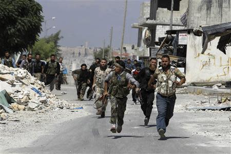 Free Syrian Army fighters run on the front line in Aleppo's Sheikh Saeed neighbourhood September 21, 2013. REUTERS/Molhem Barakat