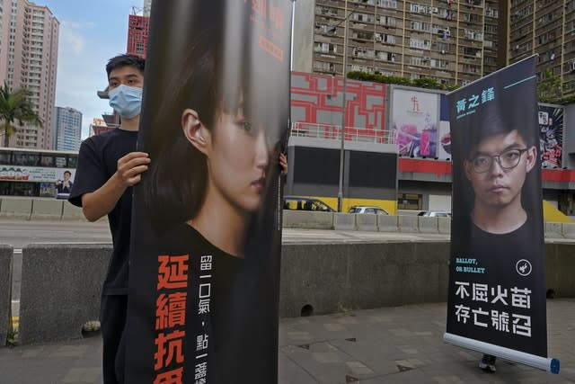Banners of pro-democracy candidates Jannelle Leung, left, and Joshua Wong are carried by supporters outside a subway station in Hong Kong (Vincent Yu/AP)