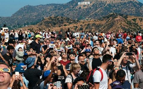 A crowd gathers in front of the Hollywood sign  - Credit: AP