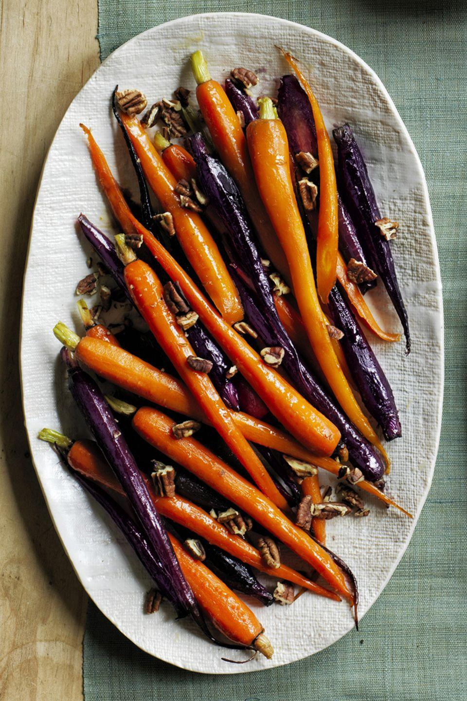 """<p>Soft and sweet, these heritage carrots add contrast to the other savory sides on your menu. </p><p><em><strong><a href=""""https://www.womansday.com/food-recipes/food-drinks/recipes/a60500/pecan-pie-glazed-carrots-recipe/"""" rel=""""nofollow noopener"""" target=""""_blank"""" data-ylk=""""slk:Get the Pecan Pie Glazed Carrots recipe."""" class=""""link rapid-noclick-resp"""">Get the Pecan Pie Glazed Carrots recipe.</a></strong></em></p>"""