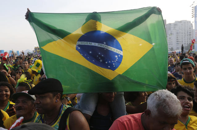 A Brazil fan holds a national flag after his team's victory during a live broadcast of the World Cup round of 16 soccer match inside the FIFA Fan Fest area on Copacabana beach, in Rio de Janeiro, Brazil, Saturday, June 28, 2014. Brazil won the match 3-2 on penalties after the match ended 1-1. (AP Photo/Silvia Izquierdo)