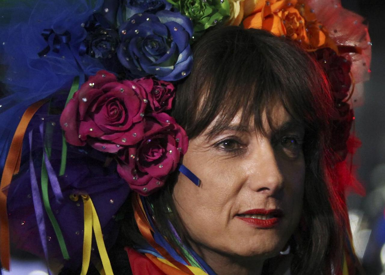 "Vladimir Luxuria, a former Communist lawmaker in the Italian parliament and prominent crusader for transgender rights, walks in Olympic Park at the 2014 Winter Olympics, Monday, Feb. 17, 2014, in Sochi, Russia. Luxuria said she was detained by police at the Olympics after being stopped while carrying a rainbow flag that read in Russian: ""Gay is OK."" Police on Monday denied this happened. (AP Photo/Steve Barker)"