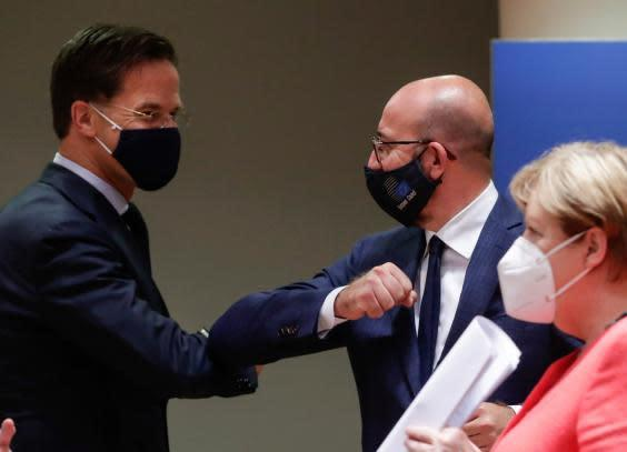 Dutch prime minister Mark Rutte, left, elbow bumps with European Council president Charles Michel as the 'breathtaking' 100-hour talks drew to a close (AP)