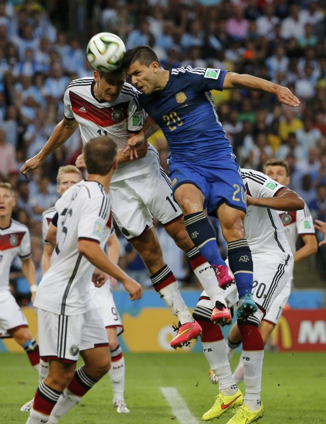Germany's Miroslav Klose jumps for the ball with Argentina's Sergio Aguero during their 2014 World Cup final at the Maracana stadium in Rio de Janeiro July 13, 2014. REUTERS/Sergio Moraes (BRAZIL - Tags: SOCCER SPORT WORLD CUP TPX IMAGES OF THE DAY)