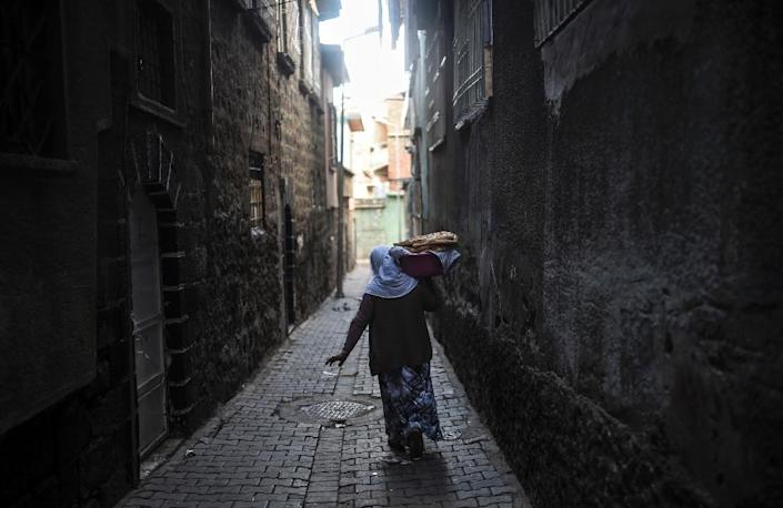 A woman carries loaves of bread in the district of Sur in Diyarbakir, southeastern Turkey, on October 31, 2015 (AFP Photo/Bulent Kilic)