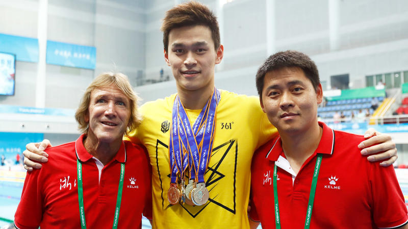 Australian coach Denis Cotterell (pictured left) smiles next to Sun yang (pictured middle) and Chinese coach Zheng Kunliang (pictured right).