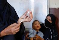 FILE PHOTO: A medical staff member fills a syringe with an anti-typhoid vaccine before administering it to a student during the immunisation campaign at a school in Karachi