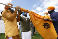 Jasbir Singh, left, and Harvinder Singh, right, assist head priest Gaini Kuldeep Singh, center, with a ceremonial changing of the Sikh flag during Vaisakhi celebrations at Guru Nanak Darbar of Long Island, Tuesday, April 13, 2021 in Hicksville, N.Y. Sikhs across the United States are holding toned-down Vaisakhi celebrations this week, joining people of other faiths in observing major holidays cautiously this spring as COVID-19 keeps an uneven hold on the country. (AP Photo/Jason DeCrow)