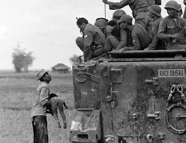 FILE - In this March 19, 1964 file photo, one of several shot by Associated Press photographer Horst Faas which earned him the first of two Pulitzer Prizes, a father holds the body of his child as South Vietnamese Army Rangers look down from their armored vehicle. The child was killed as government forces pursued guerrillas into a village near the Cambodian border. Faas, a prize-winning combat photographer who carved out new standards for covering war with a camera and became one of the world's legendary photojournalists in nearly half a century with The Associated Press, died Thursday May 10, 2012. He was 79. (AP Photo/Horst Faas)