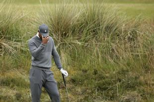 United States' Tiger Woods prepares to take a shot from the rough on the fifth hole during the first round of the British Open Golf Championship at the Old Course, St. Andrews, Scotland, Thursday, July 16, 2015. (AP Photo/Peter Morrison)