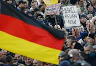 Supporters of anti-immigration right-wing movement PEGIDA (Patriotic Europeans Against the Islamisation of the West) demand the resignation of German Chancellor Angela Merkel on a placard during a demonstration rally in Cologne, Germany. Placard at L reads 'Thank you Merkel and Co. Constitutional state K.O.' Picture taken January 9. 2016. REUTERS/Wolfgang Rattay