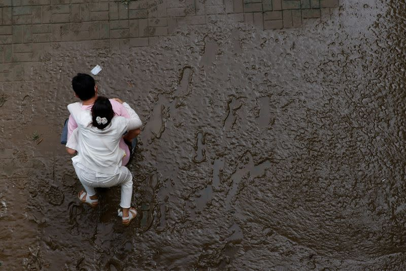 A man crosses a mud-covered trail carrying his wife on his back at a flooded Han River park in Seoul